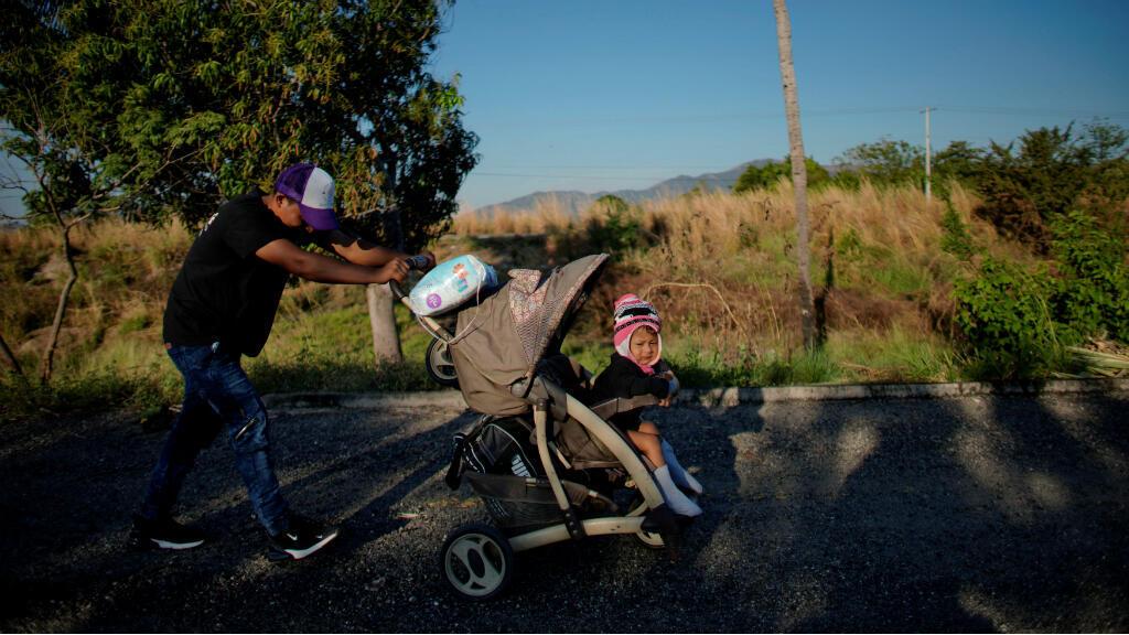 El migrante José Reyes, de 21 años, de El Salvador, empuja un carro medio roto con su hija Natali de dos años durante su viaje hacia los Estados Unidos, en Tapanatepec, México, el 21 de enero de 2019.