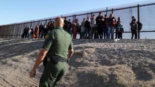 Un grupo de migrantes centroamericanos mira al agente de la Patrulla Fronteriza de EE. UU. , José Martínez, al sur de la valla fronteriza México- Estados Unidos, el 6 de marzo de 2019 en El Paso, Texas.