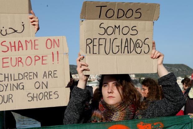 """Une volontaire manifestant au port de Lesbos tient une pancarte """"Nous sommes tous des réfugiés"""""""