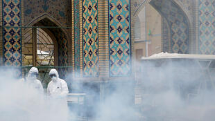 In this file photo, health workers spray disinfectant outside the Imam Reza shrine in Mashhad, Iran on February 27, 2020.