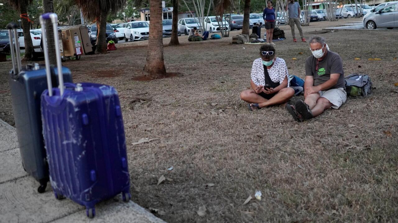 Turistas de Francia Isabele Gauthier y Paul Rogers se sientan fuera del Aeropuerto Internacional José Martí mientras deciden qué hacer después de que la aerolínea cancelara su vuelo en medio de la preocupación por la propagación del brote de la enfermedad coronavirus (COVID-19), en La Habana, Cuba, el 23 de marzo de 2020.