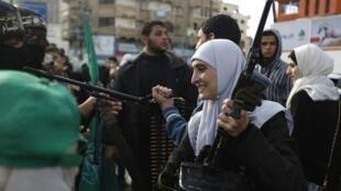 امرأة تحمل سلاحا خلال العرض العسكري لكتائب القسام في غزة بمناسبة الذكرى ال 27 لتأسيس حماس