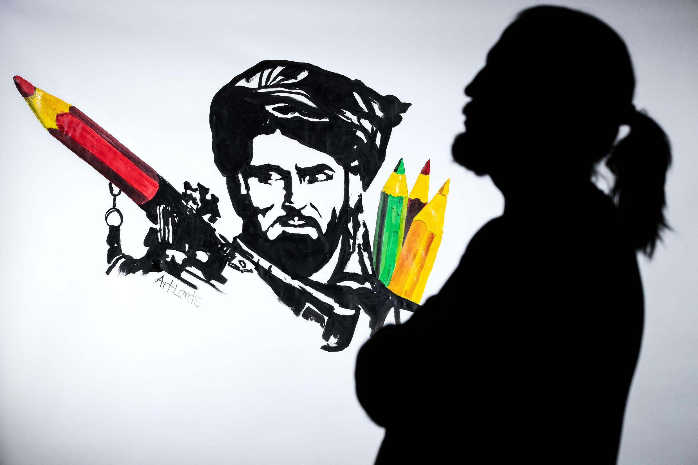 """الفنان الأفغاني فارشاد الشريك المؤسس لجمعية """"آرتلوردز"""" إلى جانب أحد أعمال المجموعة"""