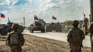 جنود أميركيون يقفون مقابل حاملات جنود روسية في محافظة الحسكة السورية بتاريخ 2 أيار/مايو 2020