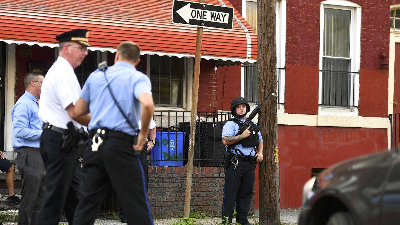 Un oficial de policía con un rifle de asalto monitorea las calles, mientras otro grupo de uniformados responde a un tiroteo, en Filadelfia, Pensilvania, el 14 de agosto de 2019