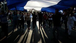 Manifestantes sostienen una gran bandera nicaragüense durante una protesta contra la violencia policial y el gobierno del presidente nicaragüense Daniel Ortega en Managua. 23 de abril de 2018.