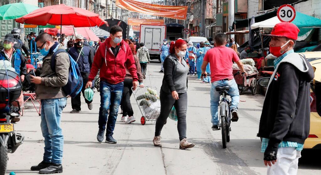 Personas pasan bajo los carteles que anuncian la alerta naranja por COVID-19, este lunes en el sector de Kennedy, en Bogotá (Colombia). Esta localidad del sur de la capital colombiana que se caracteriza por ser la más poblada ha registrado una gran cantidad de contagios de coronavirus, por lo que se decretó una cuarentena total en el sector, pero son muchas las personas que siguen saliendo.