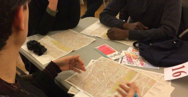 """في بلدية الدائرة العشرين بباريس يتلقى المتطوعون خرائط للطريق الذي يجب اتباعه في """"ليلة التضامن"""" . عدسة غيوم غوغين / فرانس24"""