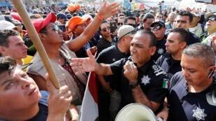 Des policiers mexicains discutent avec des migrants à proximité du poste-frontière de Charappal à Tijuana, le 22novembre2018