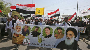 People march with a banner showing (L to R) Iraq's slain Hashed al-Shaabi commander Abu Mahdi al-Muhandis, other slain members of the group, and Iraq's top Muslim Shiite cleric Grand Ayatollah Ali al-Sistani during a symbolic funerary parade  in the capital Baghdad on June 29, 2021.