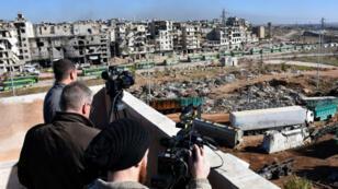 Des journalistes filmant l'évacuation des civils et des rebelles à Alep le 15 décembre 2016.