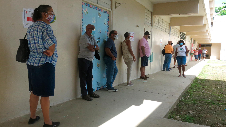 Los votantes esperan para emitir su voto en Loíza, Puerto Rico, el domingo 16 de agosto de 2020.