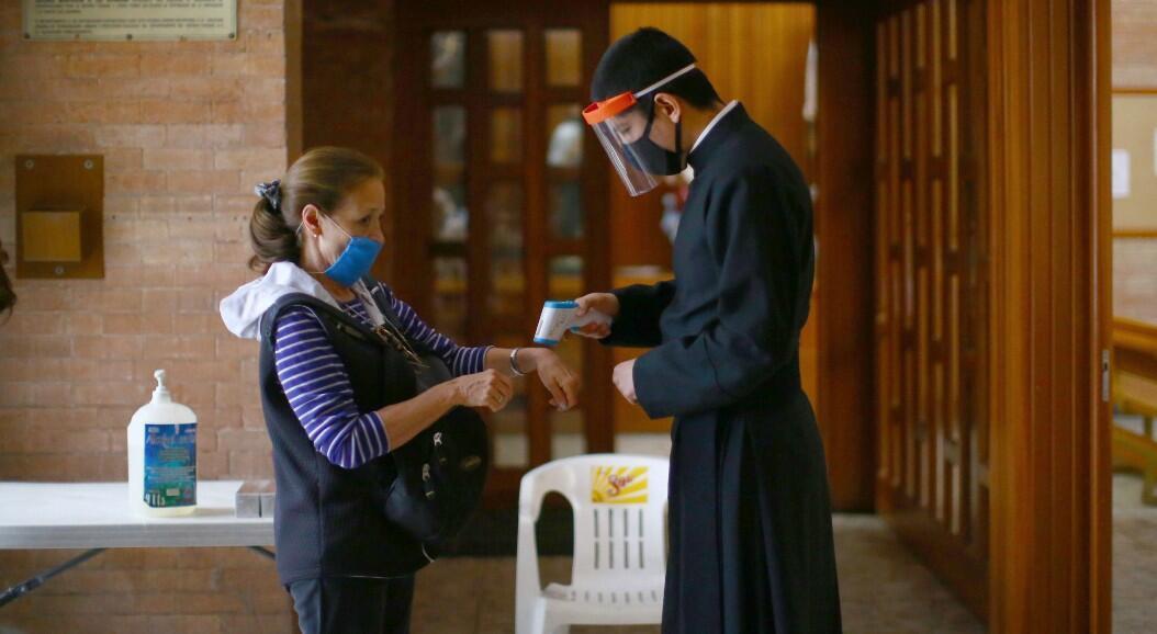 Un sacerdote revisa la temperatura de una feligrés, durante la reapertura gradual de actividades religiosas, tras meses de cierre por la pandemia. En Ciudad de México México, el 10 de julio de 2020.