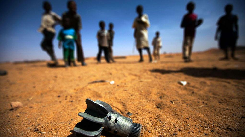 Un grupo de niños mira los restos de un obús en Sudán.
