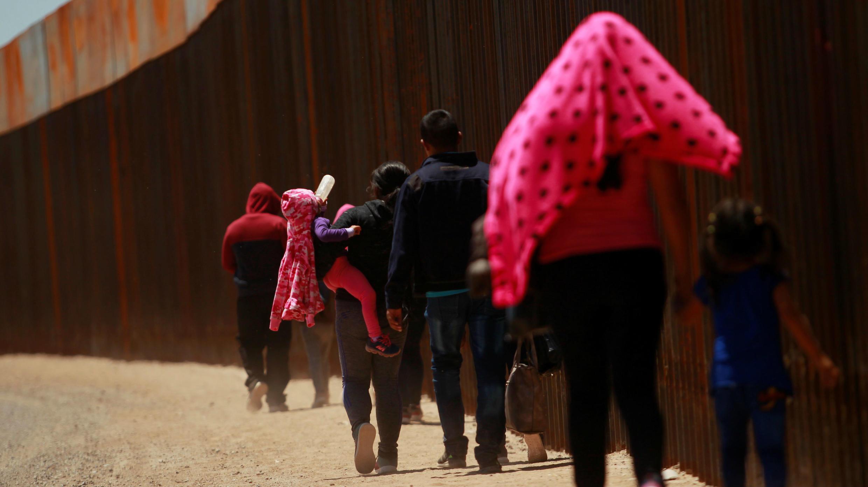 Un grupo de migrantes centroamericanos camina junto a la cerca entre México y los Estados Unidos después de cruzar la frontera en El Paso, Texas, el 15 de mayo de 2019.