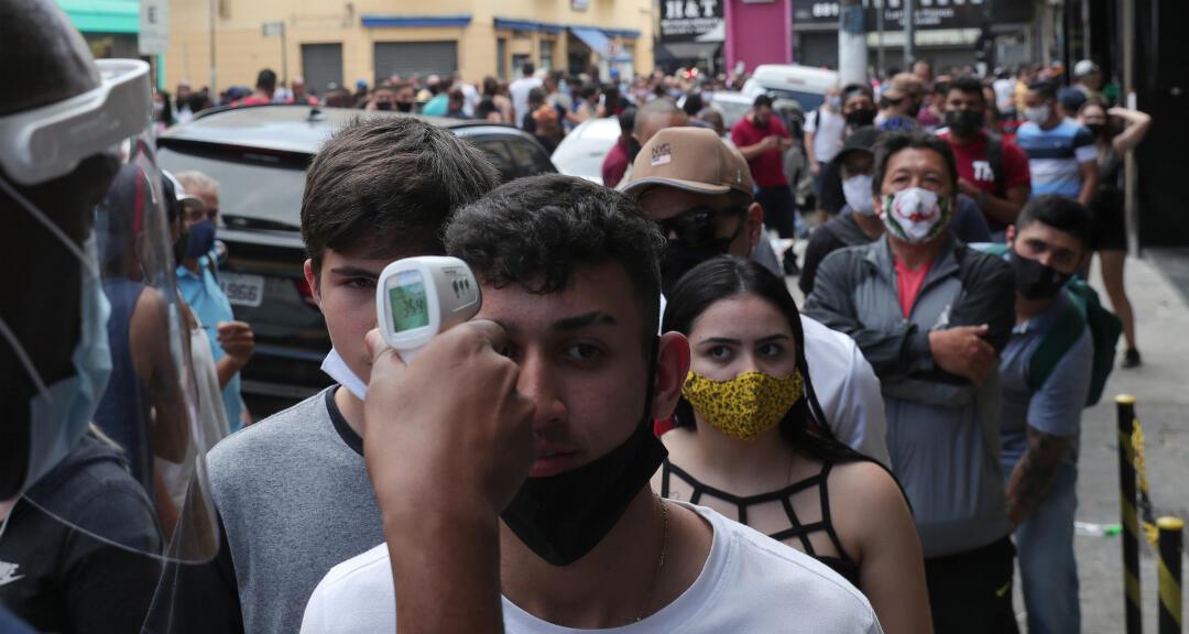 Un hombre se somete a un control de temperatura en una fila para ingresar a una tienda durante el primer día de apertura de los centros comerciales en medio del brote de coronavirus. Sao Paulo, Brasil, el 11 de junio de 2020.