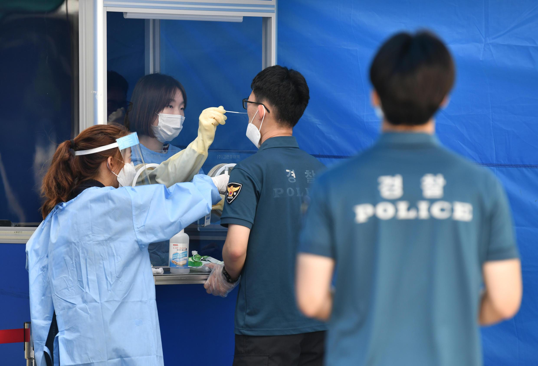 Un trabajador sanitario toma muestras para diagnosticar Covid-19 a un agente de policía en Seúl, Corea del Sur, el 19 de agosto de 2020.