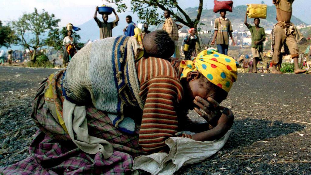 Una mujer ruandés desplazada se derrumba con su bebé sobre su espalda junto a la carretera que une el campo de refugiados de Kibumba y Goma, 28 de julio de 1994, en Kibumba, República Democrática del Congo.