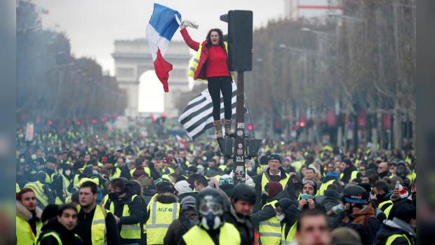 """Una manifestante de los """"chalecos amarillos"""" levanta la bandera francesa en medio de una protesta contra la subida del precio de la gasolina en los Campos Elíseos en París, Francia, el 24 de noviembre de 2018."""