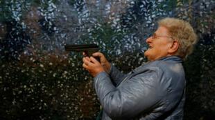 Une dame essaie un pistolet à air comprimé CO2 lors de la 45e édition de la Foire de l'armement à Lucerne, le 29 mars 2019.