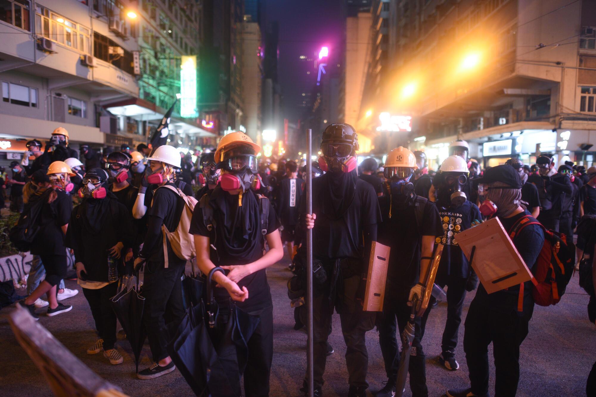 Des manifestants portent des masques à gaz, des casques et d'autres équipements de protection lors d'une manifestation à Hong Kong en septembre 2019.
