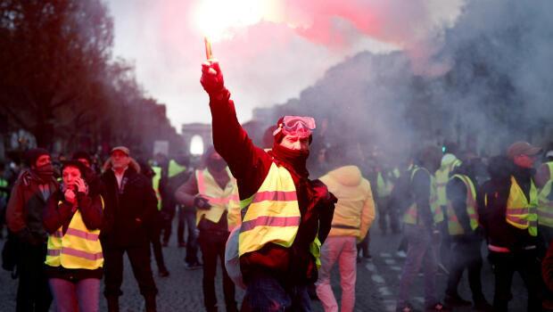 """Un manifestante de las protestas de los """"chalecos amarillos"""" contra la subida del precio de la gasolina quema una bengala en los Campos Elíseos en París, Francia, el 24 de noviembre de 2018."""