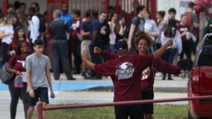 Una estudiante es abrazada cuando deja la escuela secundaria Marjory Stoneman Douglas después de asistir a sus clases por primera vez desde el tiroteo que mató a 17 personas el 14 de febrero en la escuela el 28 de febrero de 2018 en Parkland, Florida.