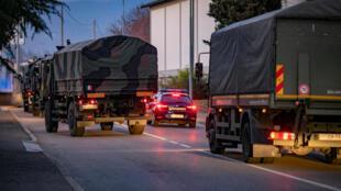 Des camions militaires circulent dans la ville de Bergame pour acheminer les corps défunts dans les provinces voisines et permettre leur inhumation, le 18 mars 2020.