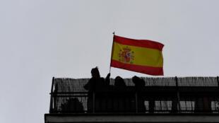 Una persona sostiene una bandera de España en su terraza durante una protesta contra la gestión del gobierno en la crisis del coronavirus, el 14 de mayo de 2020 en Madrid