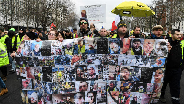 Protesters hold a banner with pictures of people purportedly injured by police during a Yellow Vest protest in Paris on January 26, 2019.