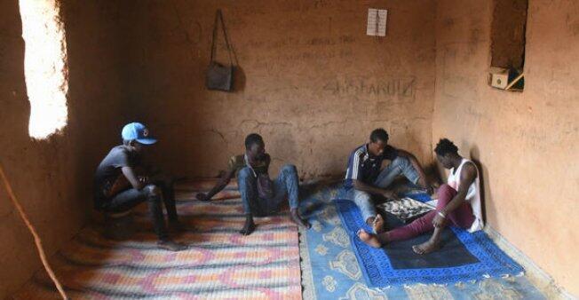 أرنو زوكو (الثاني على اليمني) يتسلى مع مهاجرين اخرين في انتظار السفر إلى ليبيا صورة للصحفي مهدي شبيل