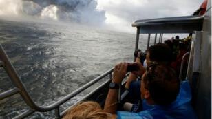 La gente mira desde un bote turístico mientras la lava fluye hacia el Océano Pacífico en el área de Kapoho, al este de Pahoa, durante las erupciones en curso del volcán Kilauea en Hawaii, EE. UU., 4 de junio de 2018.