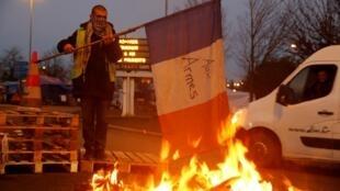 """Un 'chaleco amarillo' protesta con una bandera que cita la Marsellesa: """"A las armas, ciudadanos"""", el 4 de diciembre de 2018 en la carretera que une París Con Bruselas en Fontaine-Notre Dame."""