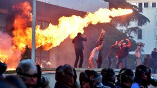 Las llamas se generan detrás de una formación policial durante una protesta antigubernamental frente a la oficina del Primer Ministro Edi Rama en Tirana, Albania , el 11 de mayo de 2019.