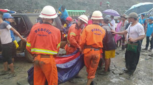 Rescue workers carry a dead body following a landslide at a mining site in Hpakant, Kachin State City, Myanmar on July 2, 2020, in this picture obtained from social media.