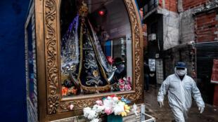 Un hombre con ropa de seguridad camina frente a una virgen, este lunes, en el barrio Fraga de Chacarita, en la Ciudad de Buenos Aires (Argentina), el 8 de junio de 2020.