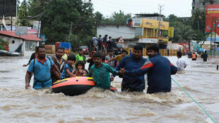 Voluntarios y personal de rescate evacúan a los residentes locales en un bote en una zona residencial de Aluva en el distrito de Ernakulam, en el estado indio de Kerala. 17 de agosto de 2018.