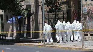 Miembros de la Policía de Investigaciones (PDI) de Chilerevisan la zona donde se produjo una explosión en el centro de Santiago (Chile).