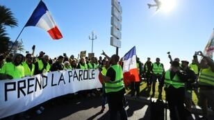"""Protestors hold a banner reading """"The people speak out"""" during a protest of 'yellow vests' against rising fuel prices and living costs, in the southern French city of Nice on December 8, 2018"""
