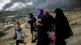 عائلات نازحة في القيارة في جنوب الموصل ويبدو الدخان الناتج عن الحرائق