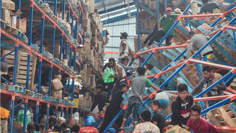 Las víctimas de los fenómenos naturales buscan productos en un almacén en Palu.