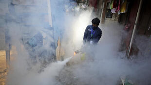 A worker fumigates a slum to prevent an outbreak of dengue fever in Jakarta, Indonesia, Wednesday, April 22, 2020.