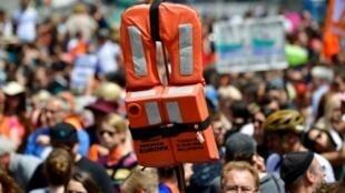 متظاهر يحمل سترة انقاذ خلال تظاهرة تندد باغلاق موانىء البحر المتوسط امام المهاجرين في برلين في 7 تموز/يوليو 2018