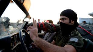 Un combattant peshmerga qui passe le poste-frontière de Habur, en Turquie, dans un convoi chargé d'armes lourdes.