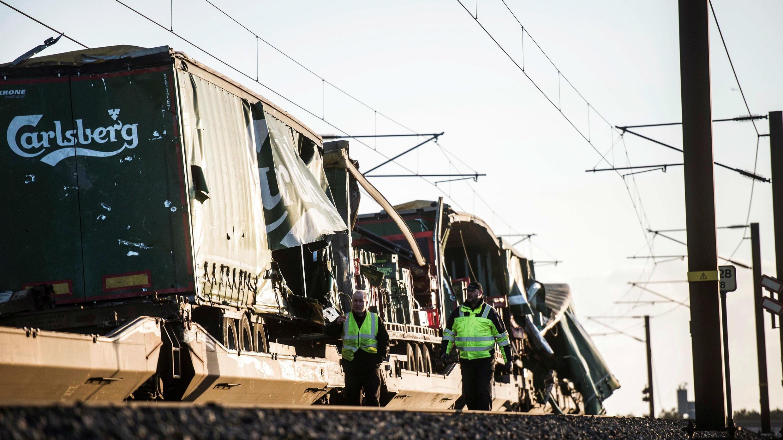 Varios operarios pasan junto un tren de carga en el puente que cruza el estrecho del Gran Belt en Nyborg - Dinamarca, en donde se registró el accidente ferroviario. 02/01/2019
