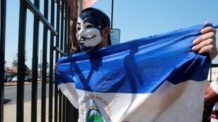 Un manifestante antigubernamental sostiene una bandera nicaragüense y grita consignas a la policía antidisturbios durante una protesta contra el gobierno del presidente de Nicaragua, Daniel Ortega, en Managua, Nicaragua, el pasado 30 de marzo de 2019.