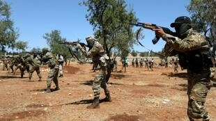 Syrian fighters fire AK-47 rifles as they attend a mock battle in anticipation of an attack by the regime on Idlib province during a graduation of new Hayat Tahrir al-Sham (HTS) members in Idlib province on August 14, 2018