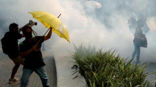 Des manifestants sous les gaz lacrymogènes tirés par la police lors d'un nouvelle journée de protestation, le 27octobre2019 à HongKong.
