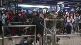 Carabineros de la Policía chilena retienen a un manifestante en la estación del metro Los Héroes el viernes 18 de octubre, en Santiago, Chile.