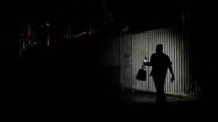 Un residente usa la luz de un teléfono celular mientras camina por una calle durante un apagón en Caracas, Venezuela, el 26 de marzo de 2019.